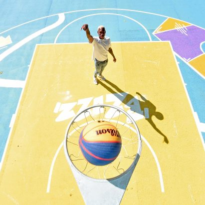 a man shoots a ball into a hoop on a basketball court