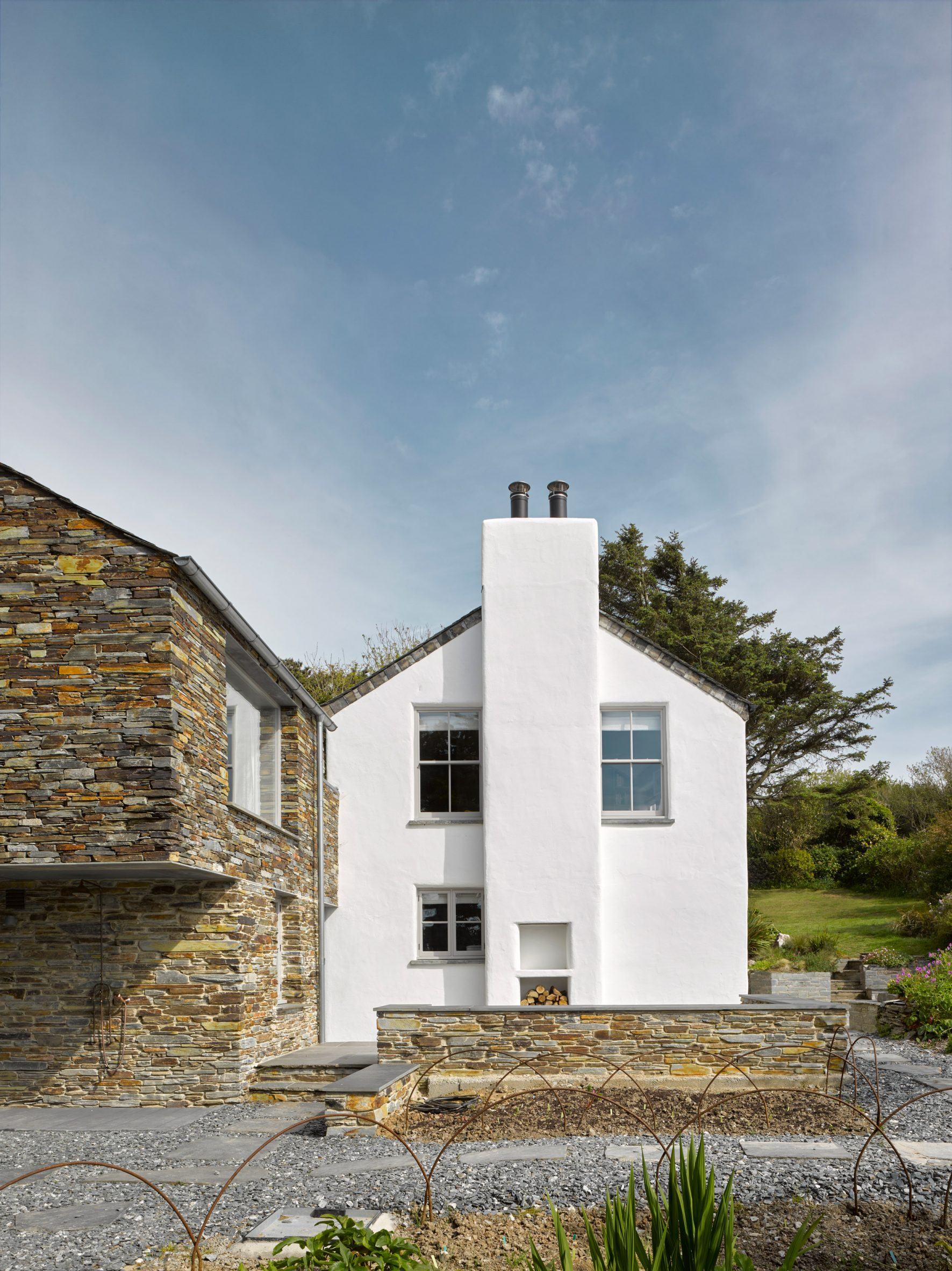 A white house with a stone extension