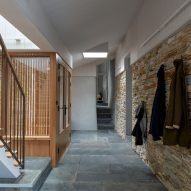 A residential hallway with a stone wall
