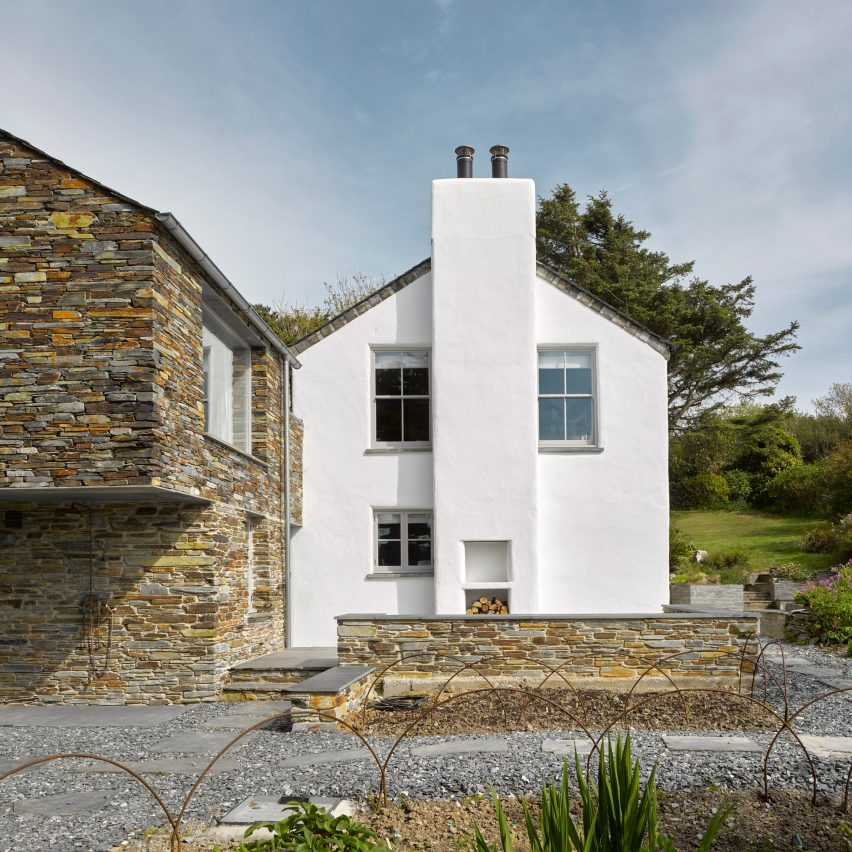 A white house with a stone-clad extension