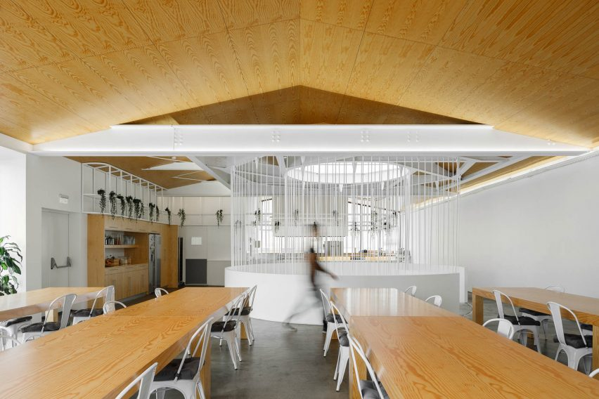 Desks and wooden ceiling on top floor of E-goi and Clavel's Kitchen office by Paulo Merlini Architects