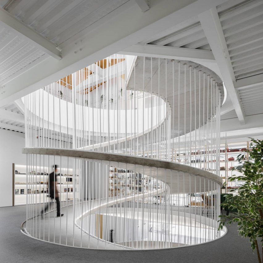 Spiralling concrete ramp in E-goi and Clavel's Kitchen by Paulo Merlini Architects