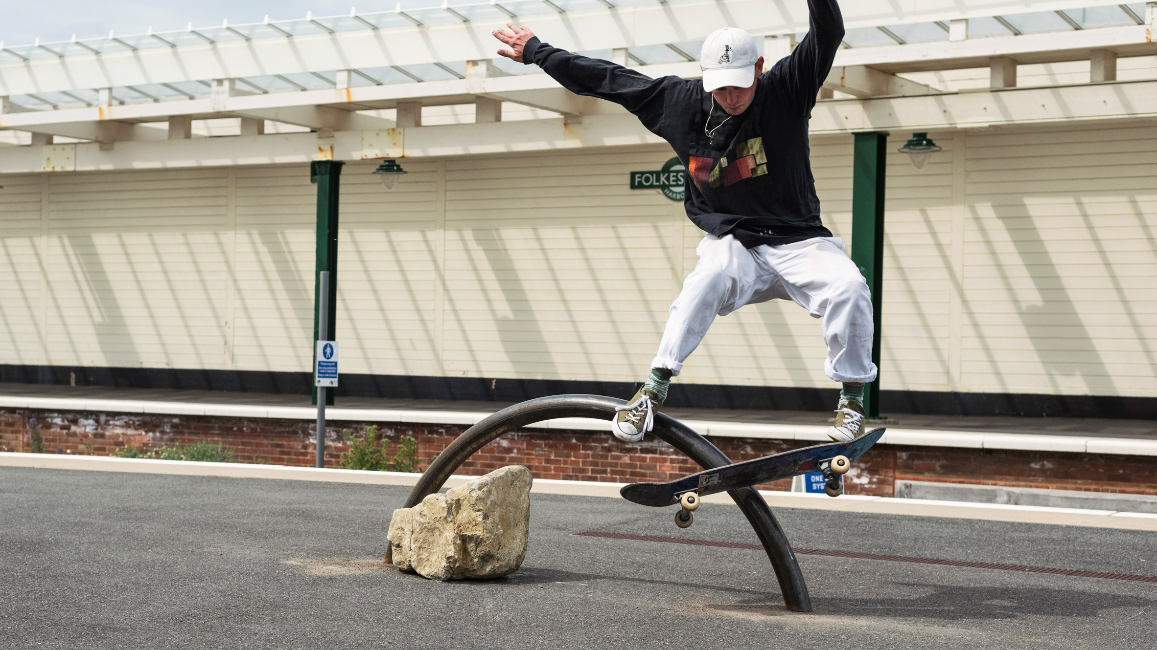 Skater performing a trick on a rainbow-shaped sculpture by Assemble at the Folkestone Triennial 2021