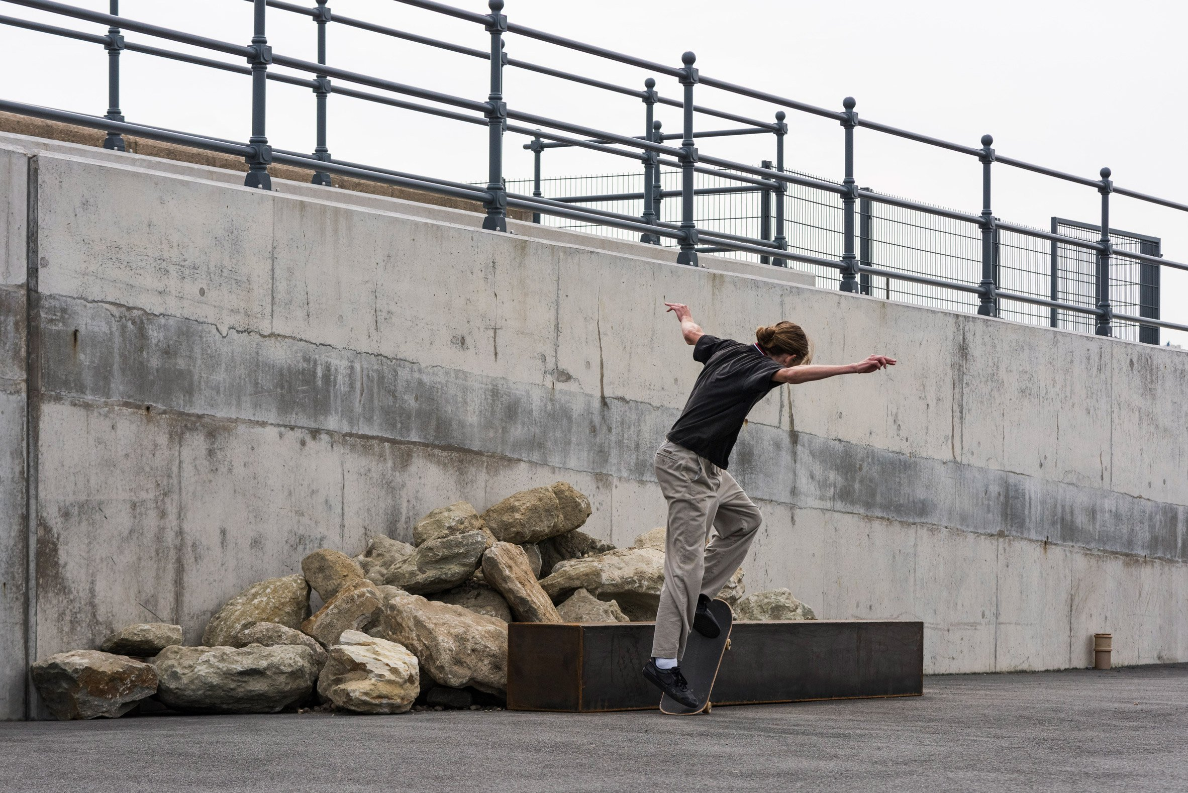 Skater on a steel box tube in front of stones in Skating Situations installation by Assemble
