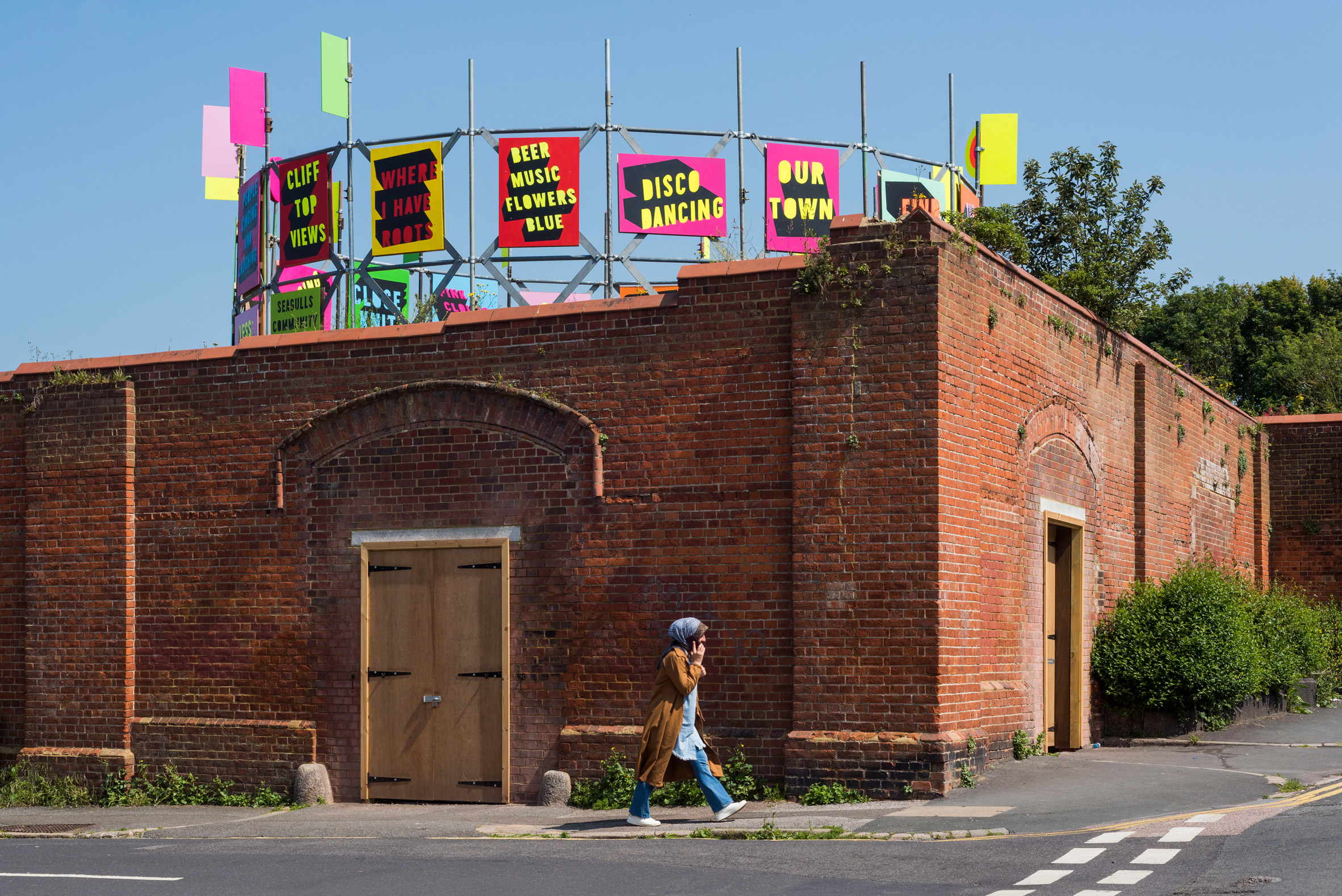 Colourful gasworks installation by Morag Myerscough behind a red brick wall at Folkestone Triennial 2021