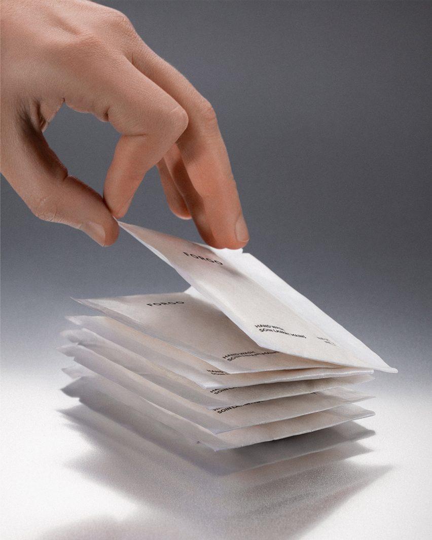 Рука хватает пакетик с порошкообразным мылом