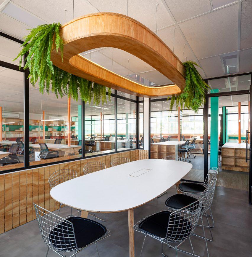 Digantung di atas meja makan adalah instalasi pencahayaan kayu yang dapat menampung tanaman pot