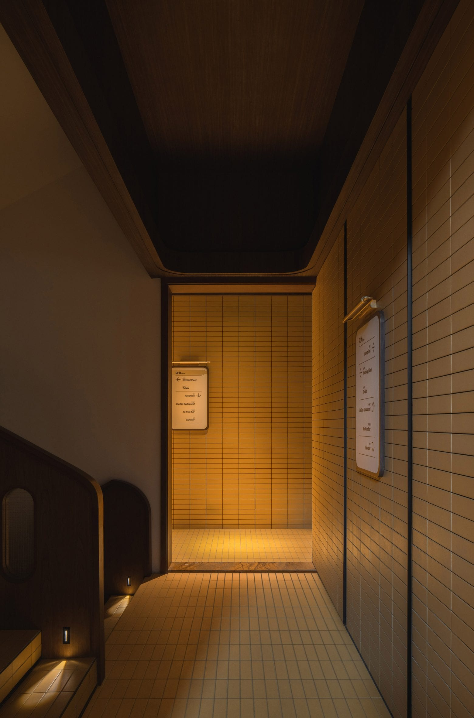 Yellow-tiled hallway with mellow lighting in hotel by Archetype