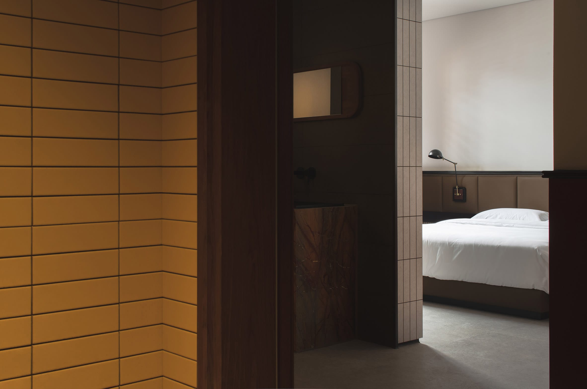 Yellow-tiled hallways and bed with white sheets in hotel interior by Archetype