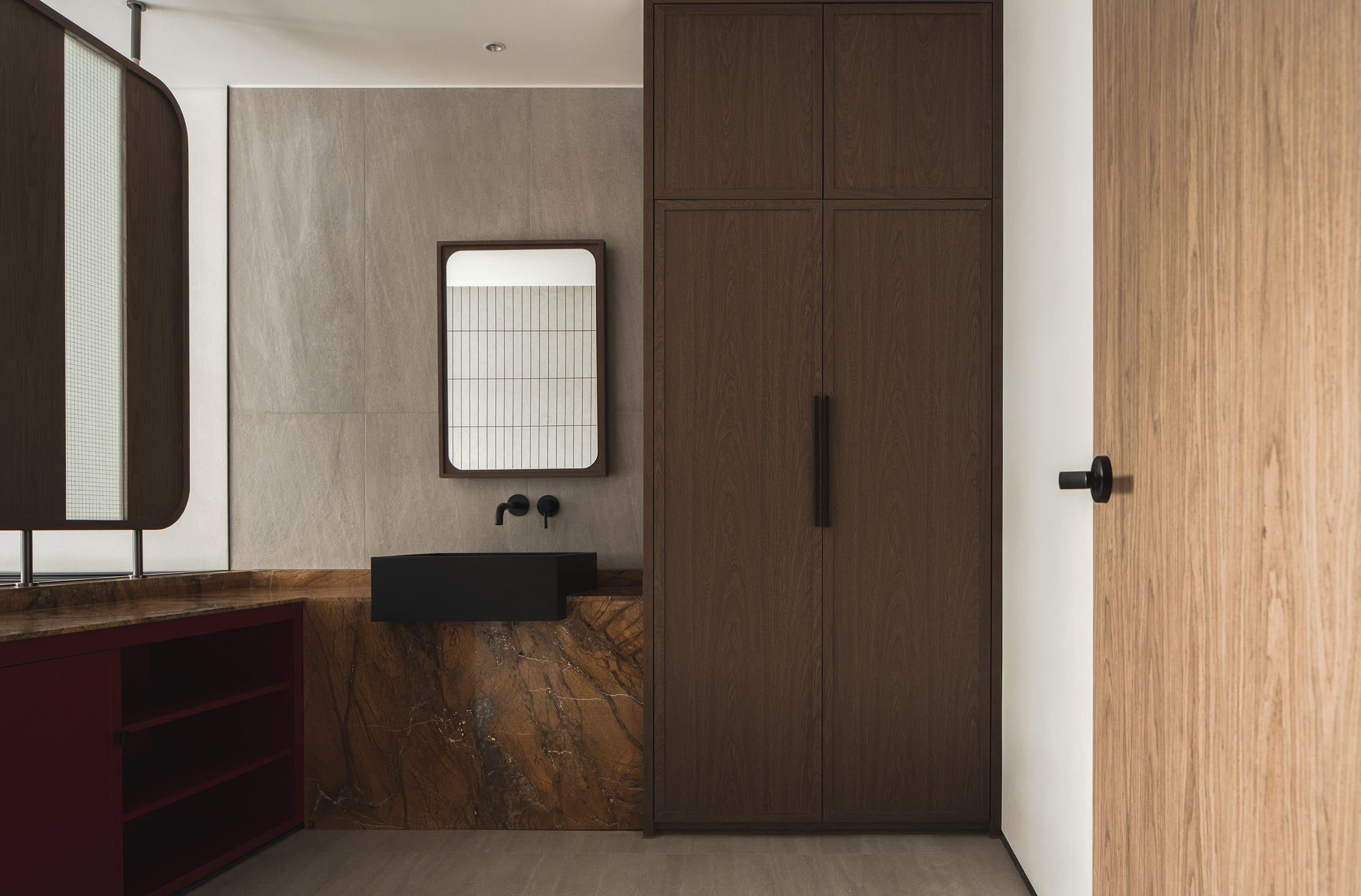 Wooden doors and red stone counters in bathroom of Buda Hotel