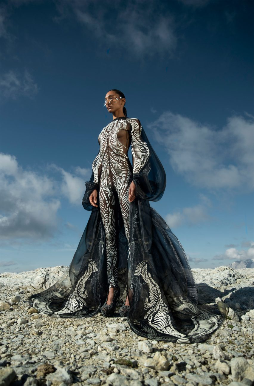 A woman standing on rocks in a look from the Earthrise collection