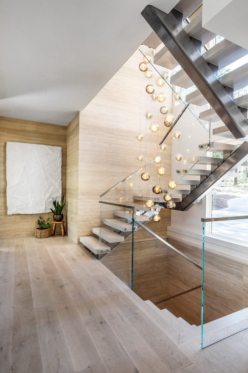 A set of orbed pendant lights handing above a staircase