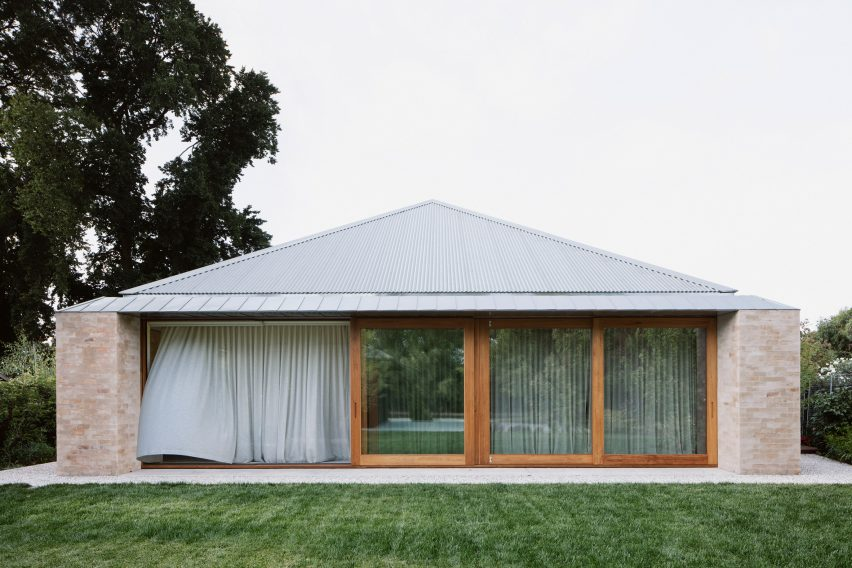 A brick house with a pyramidal roof
