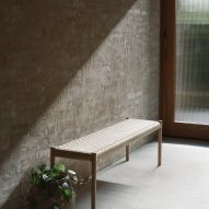 A wooden bench against a pale brick wall