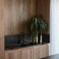 An kitchen with wooden cabinetry and a black sink