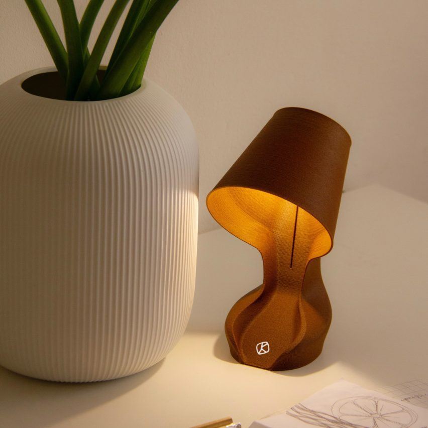 an ohmie lamp next to a plant pot