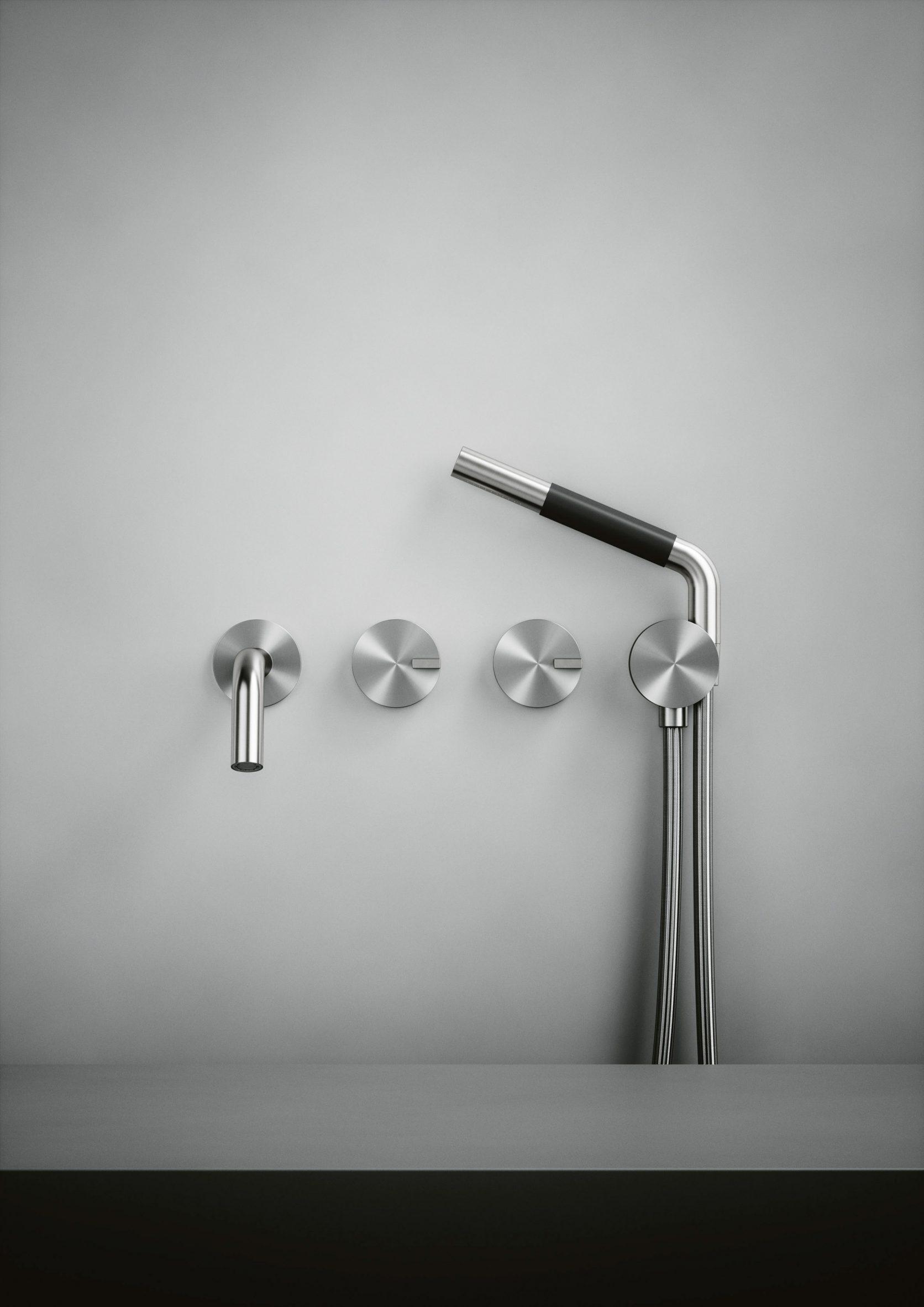 A silver showerhead and bath tap