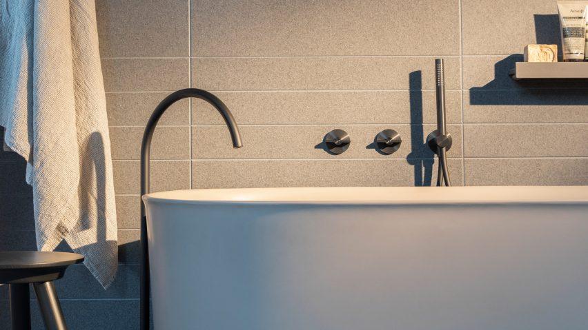A white bath and steel sink inside a bathroom