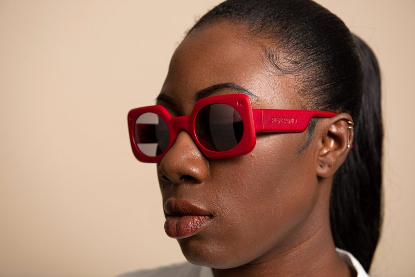 A woman wearing a red pair of sunglasses