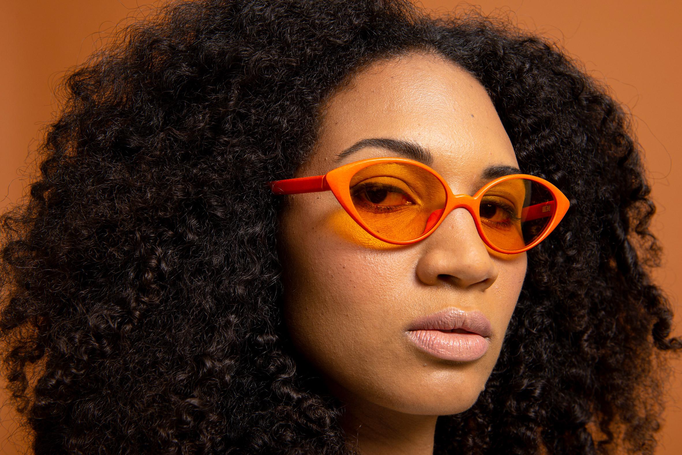 A woman wearing an orange pair of Reframd sunglasses