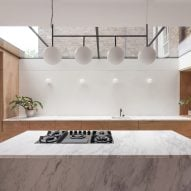 A marble kitchen island and wooden cabinetry
