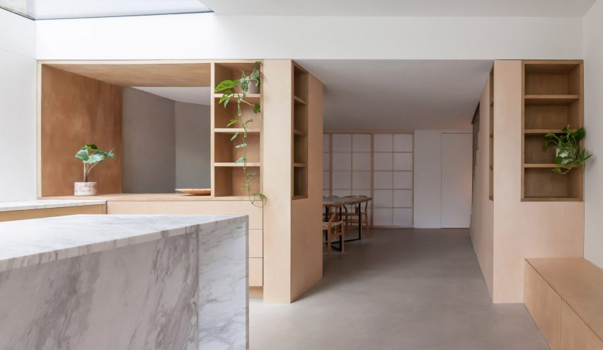 A white kitchen with a marble island and wooden cabinets