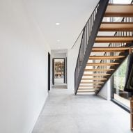 A white-walled hallway with a timber staircase