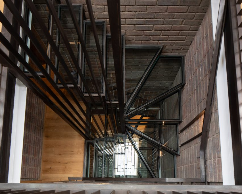 A blackened steel and glass staircase under a skylight