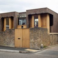 Southwark Brick House peeks above a brick wall in Bermondsey
