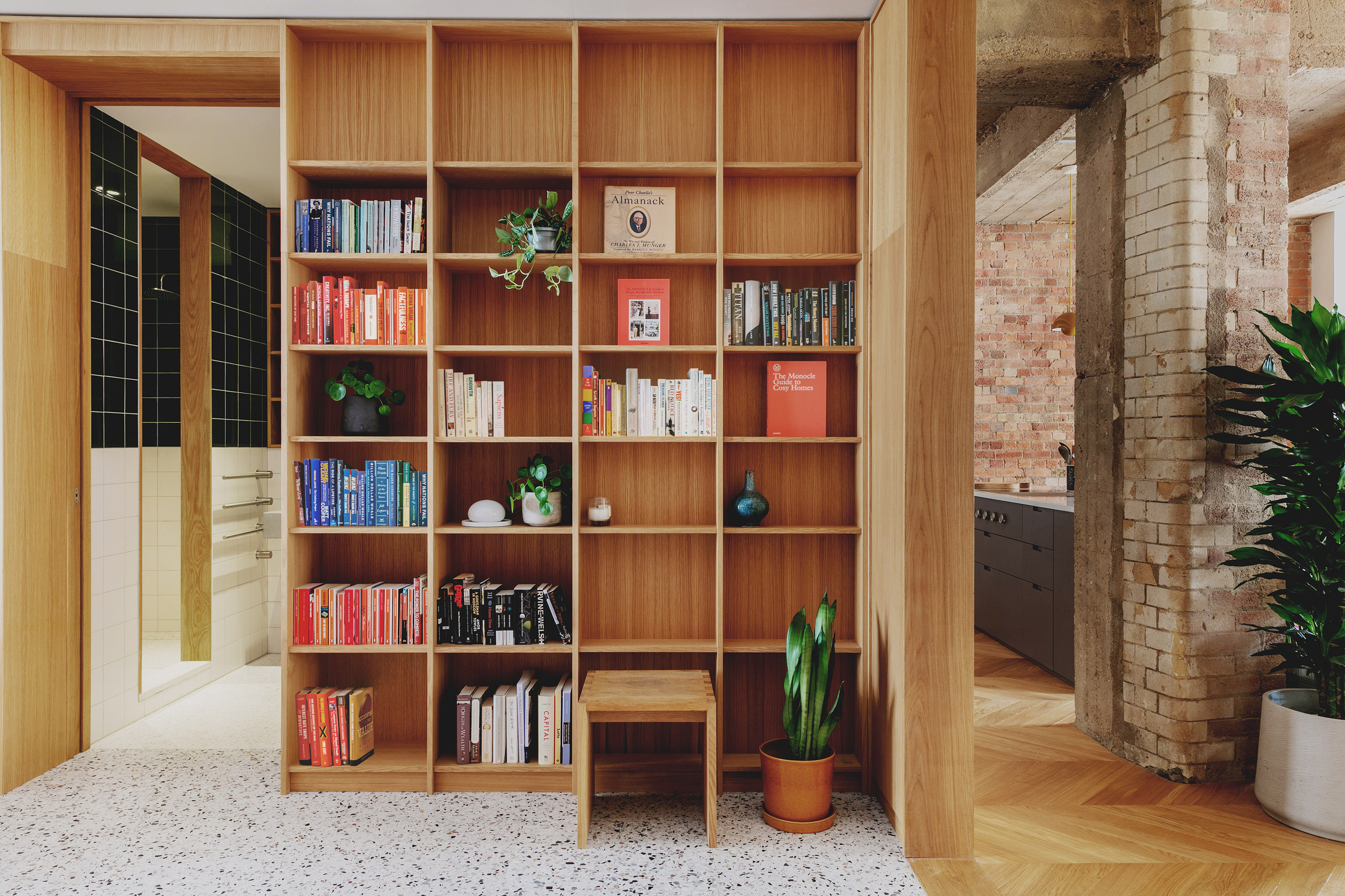 Entrance library with oak shelving in St John Street warehouse apartment by Emil Eve Architects