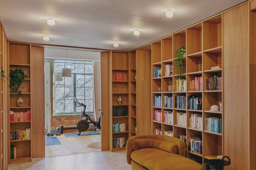 Pocket Doors and Entrance Bookcase in St John Street Warehouse Apartment by Emil Eve Architects