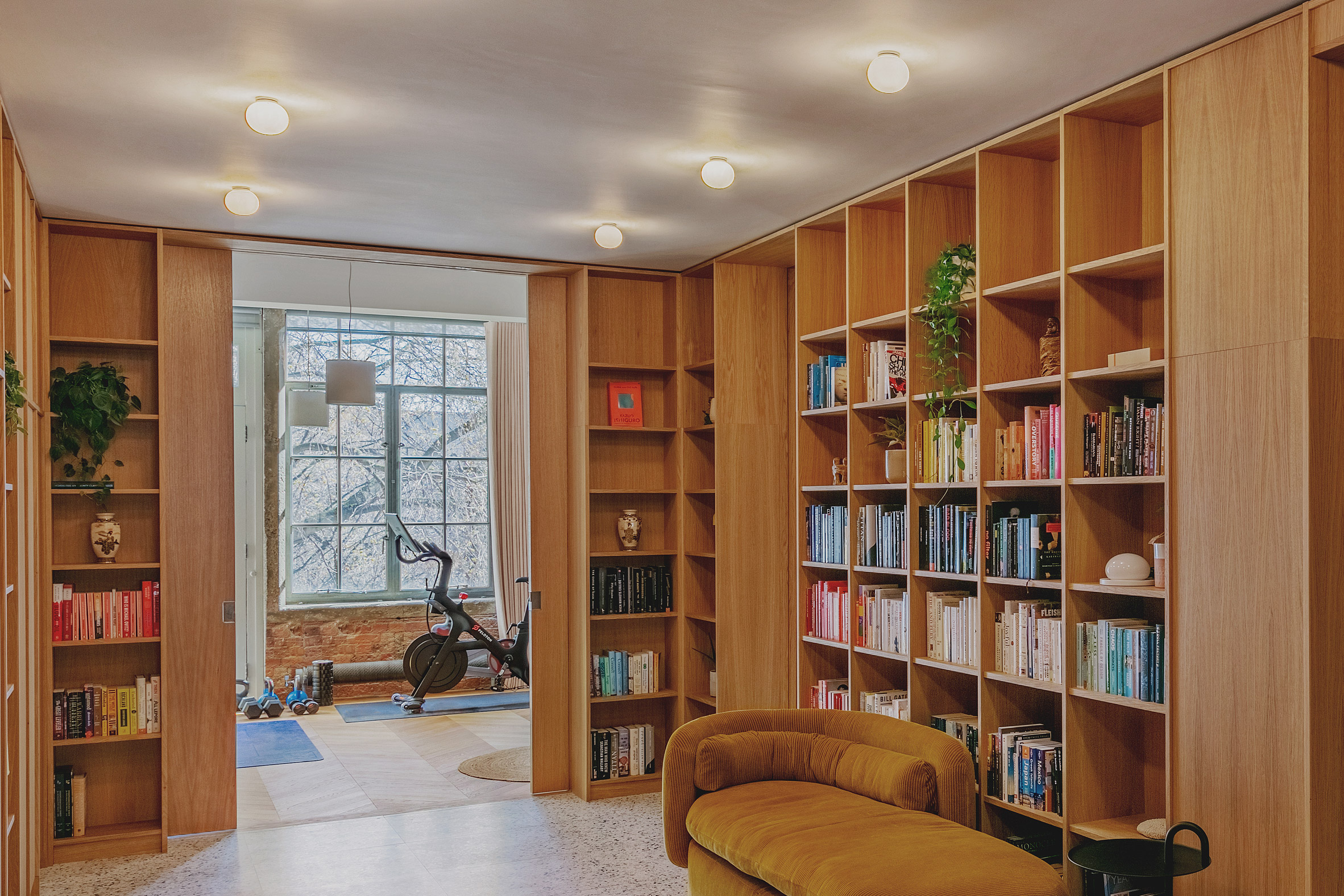 Pocket doors and entrance library in St John Street warehouse apartment by Emil Eve Architects