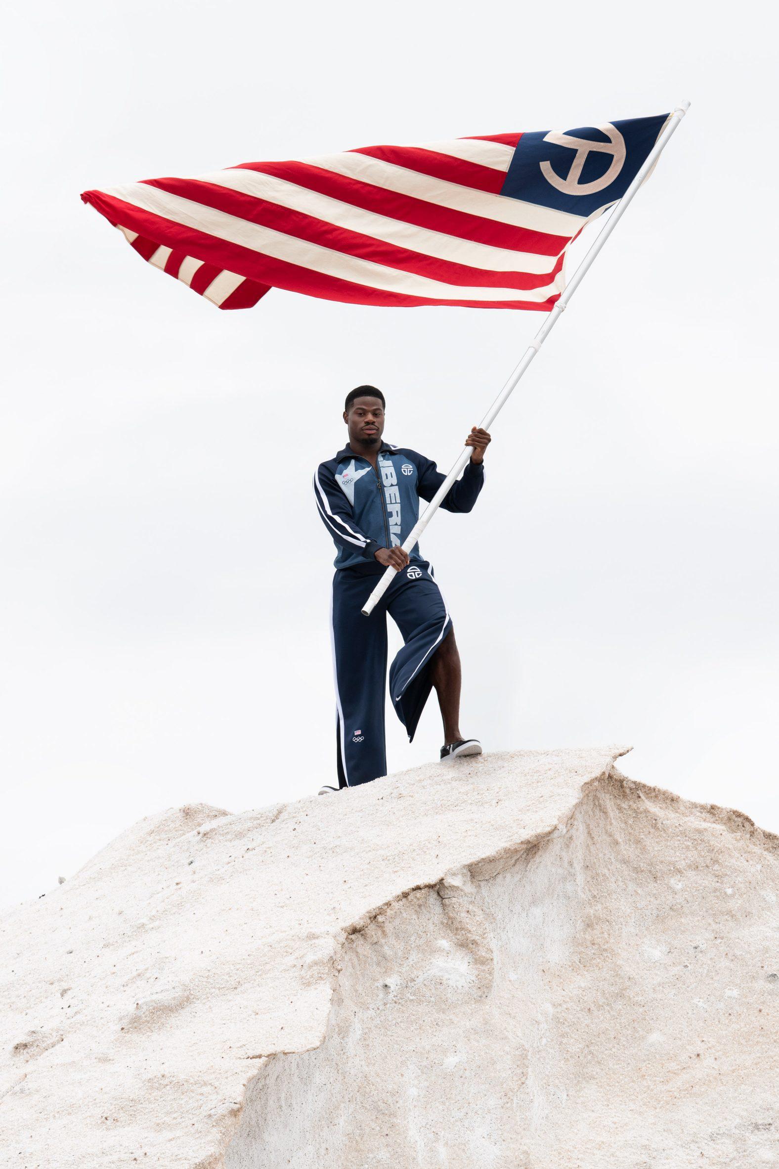 A man waves a flag while wearing the Telfar Olympic uniform
