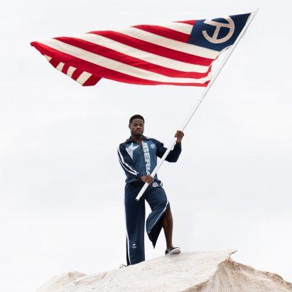 a man waving the liberian flag wearing telfar olympic uniform