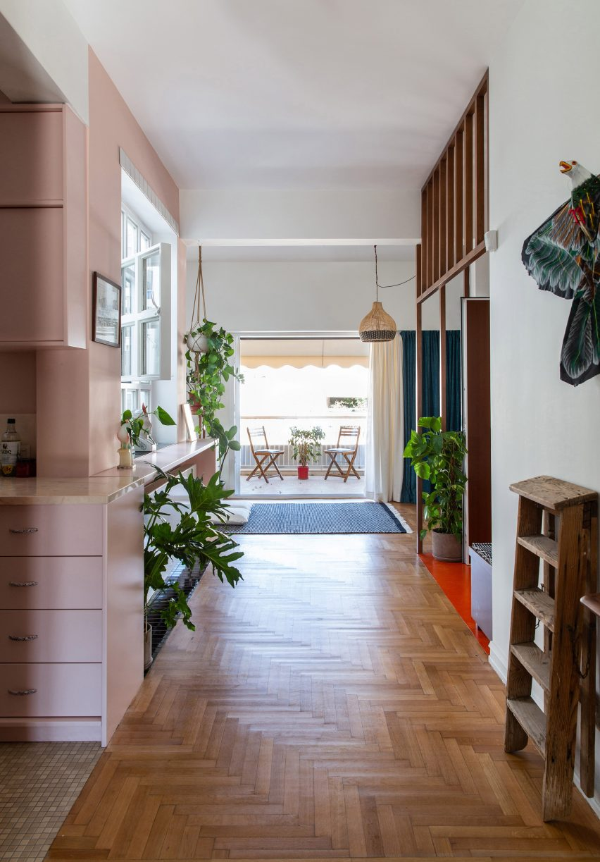 Apartment with wooden floors and pink storage by Point Supreme Architects