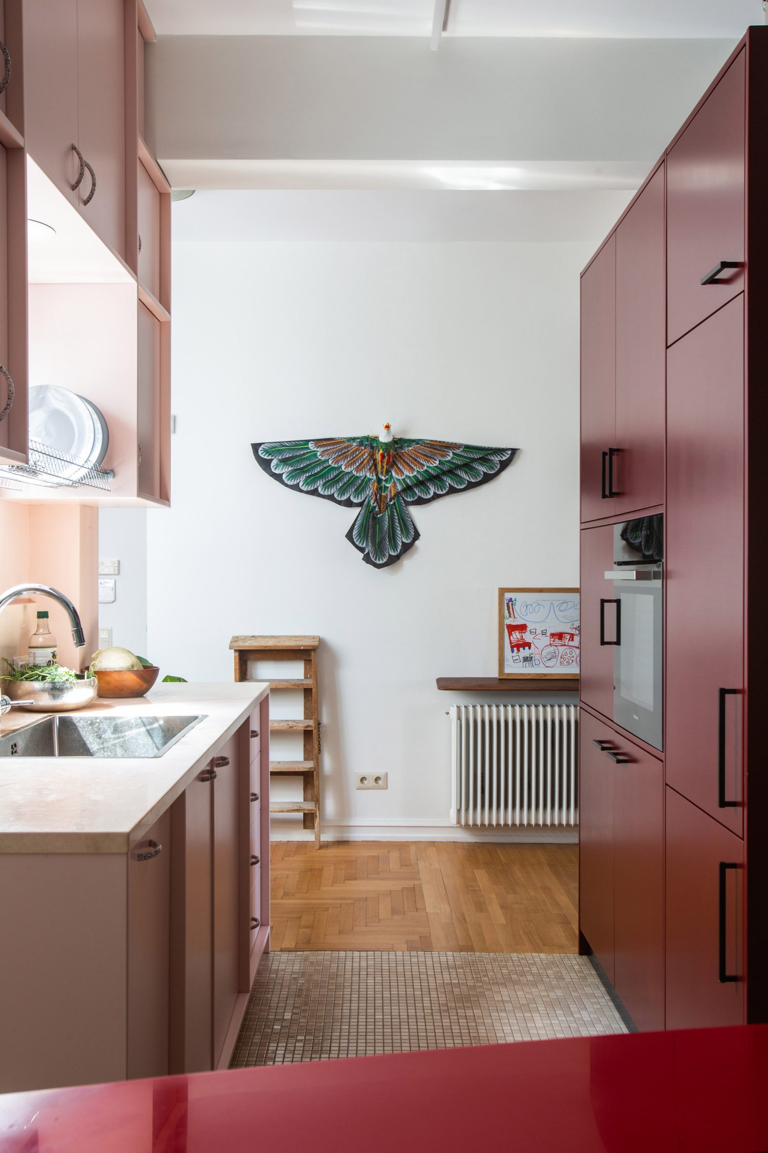 Pink-toned kitchen with wooden floors by Point Supreme Architects