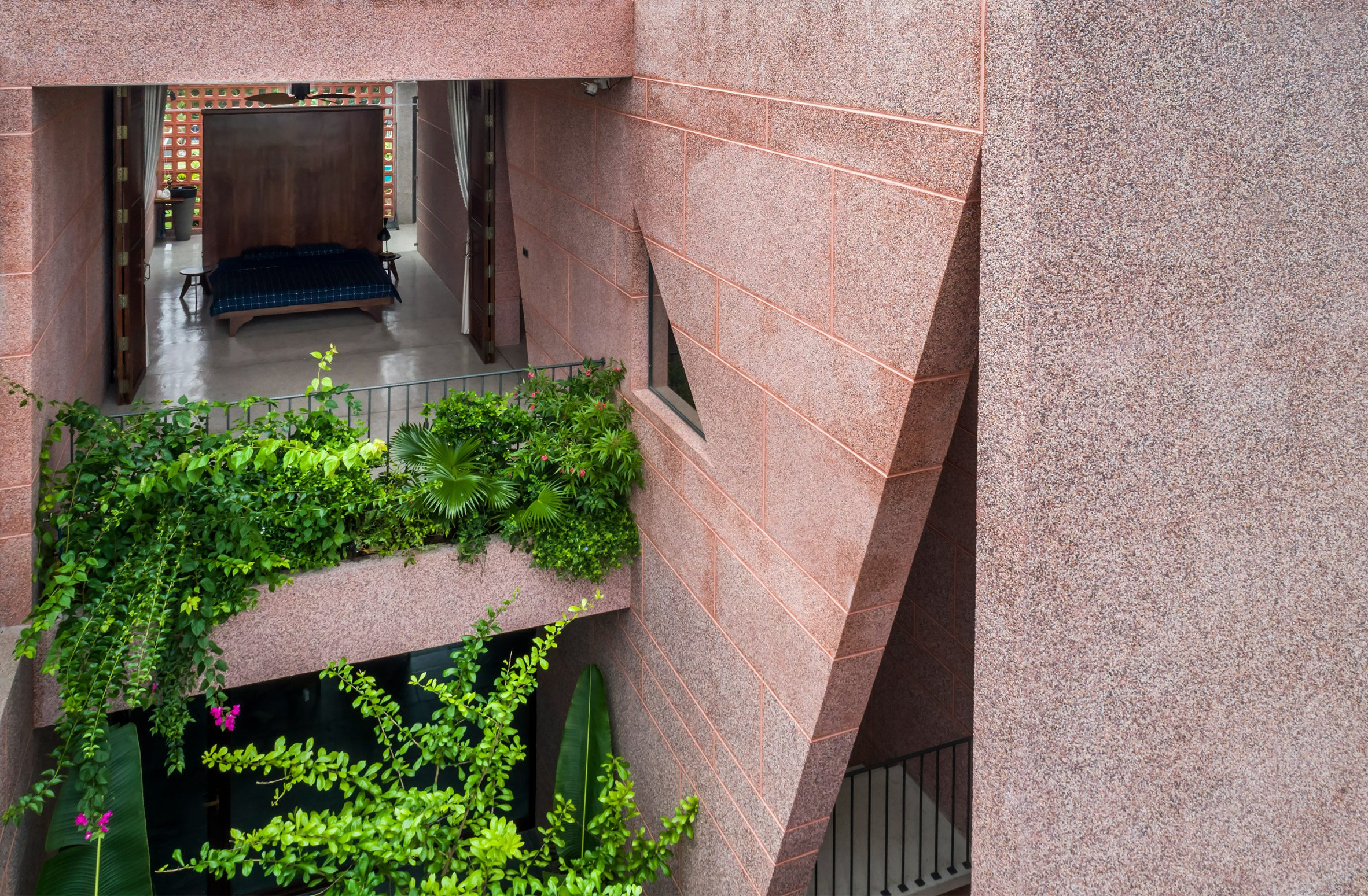 Planted balconies are adjoined to the bedrooms of pink house