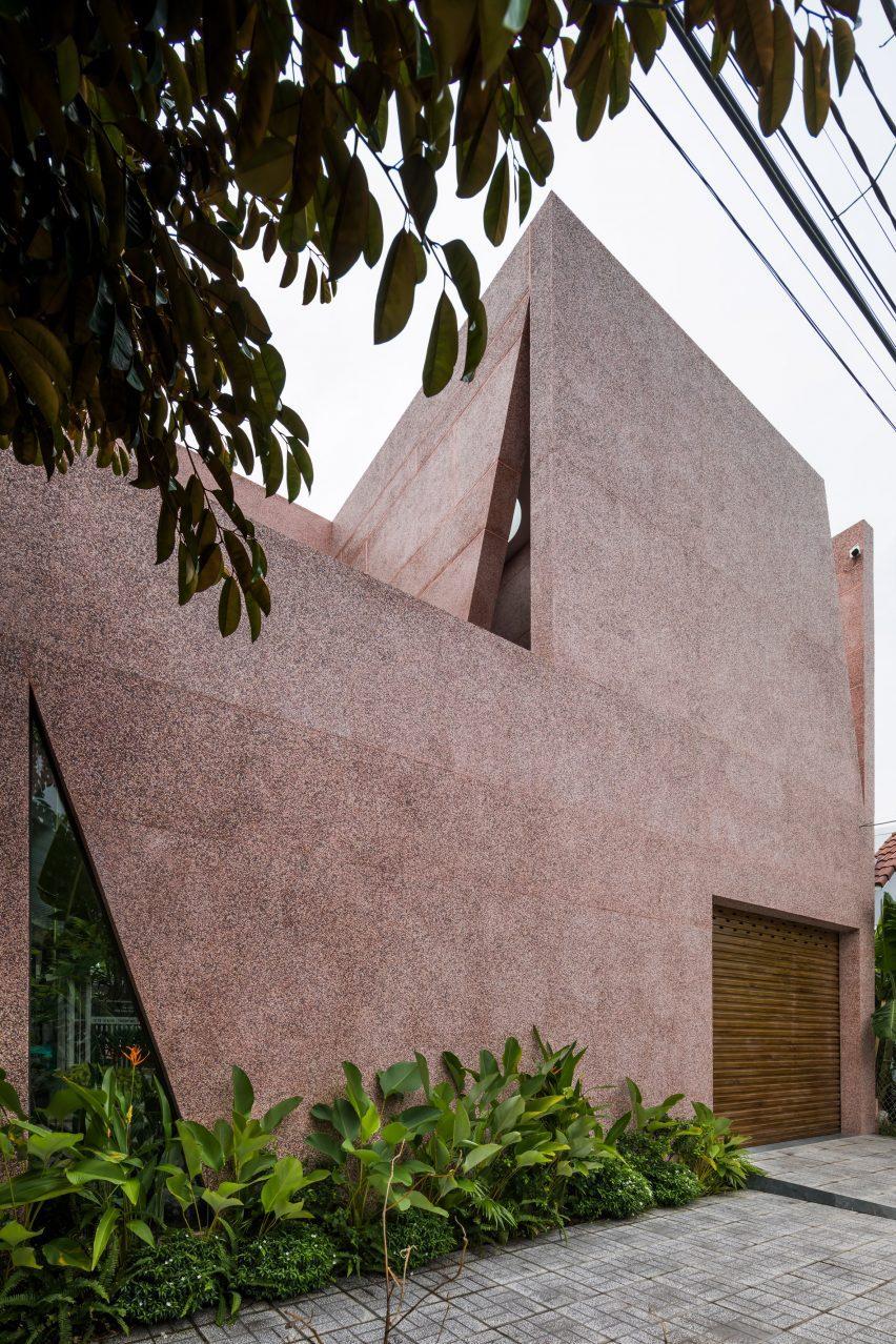 Розовый дом имеет внешнюю отделку из гальки.