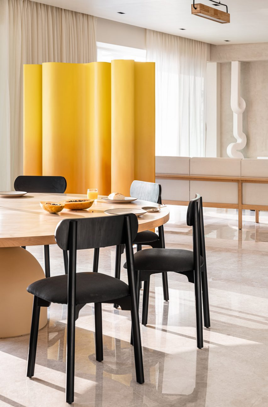 Dining room with wooden table, black chairs and wavy partition wall in yellow by The Act of Quad