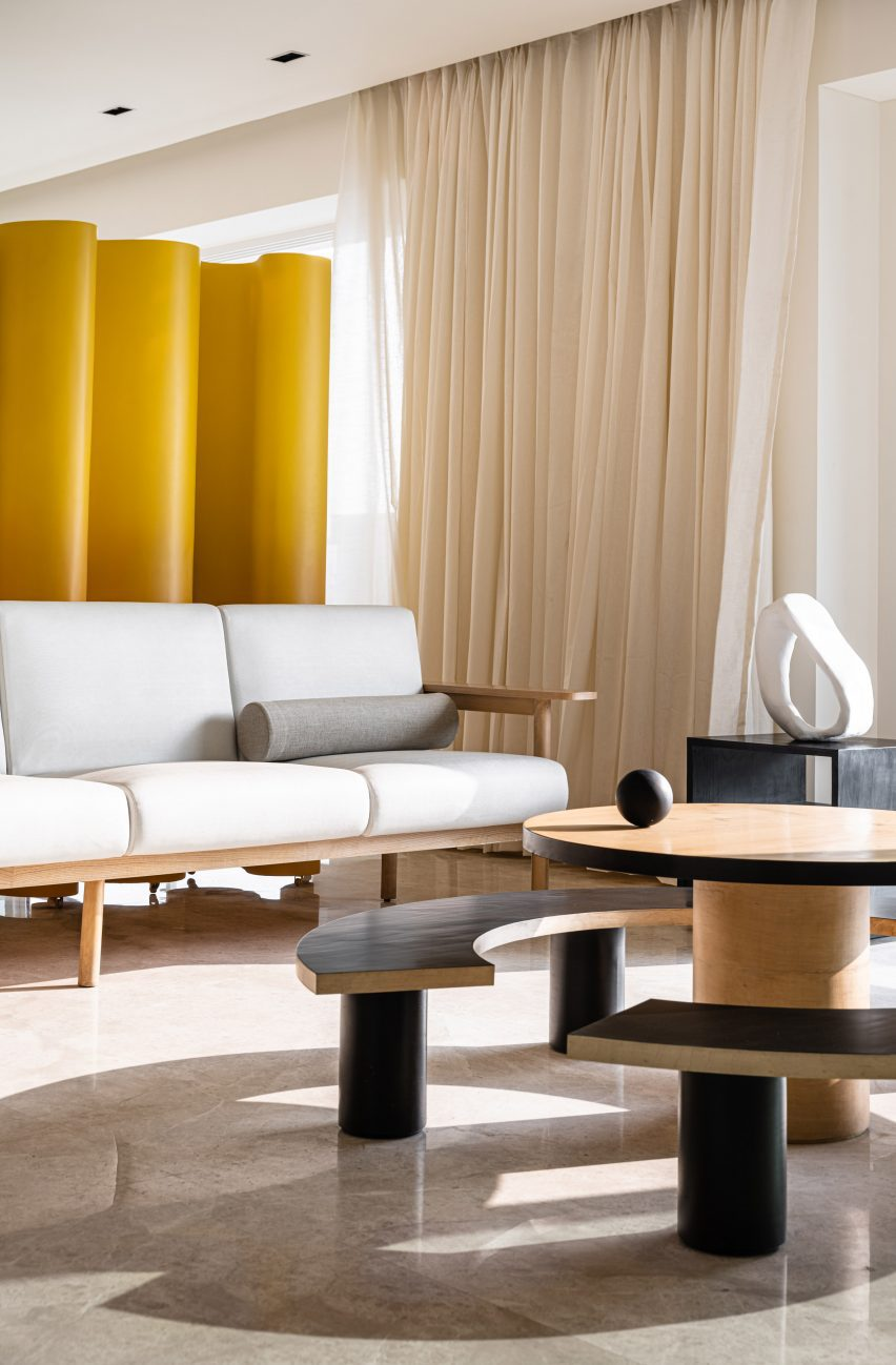 White couch with wooden coffee table and curved bench by The Act of Quad