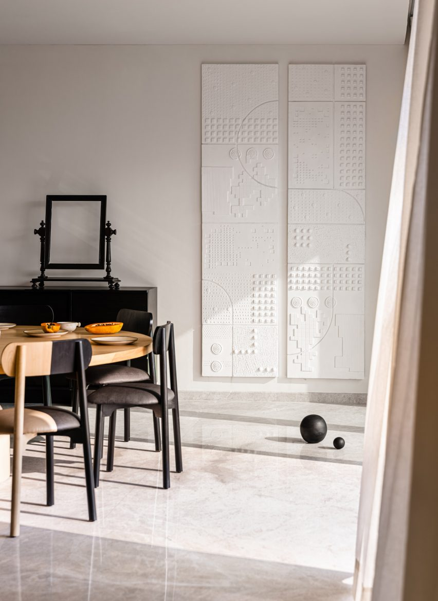 Dining table setup next to white gypsum artwork and black sphere on the floor in Mumbai apartment