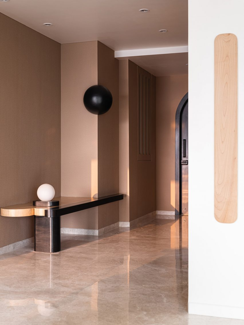 Entrance hall with brown painted walls and wooden console with white sphere in Mumbai apartment