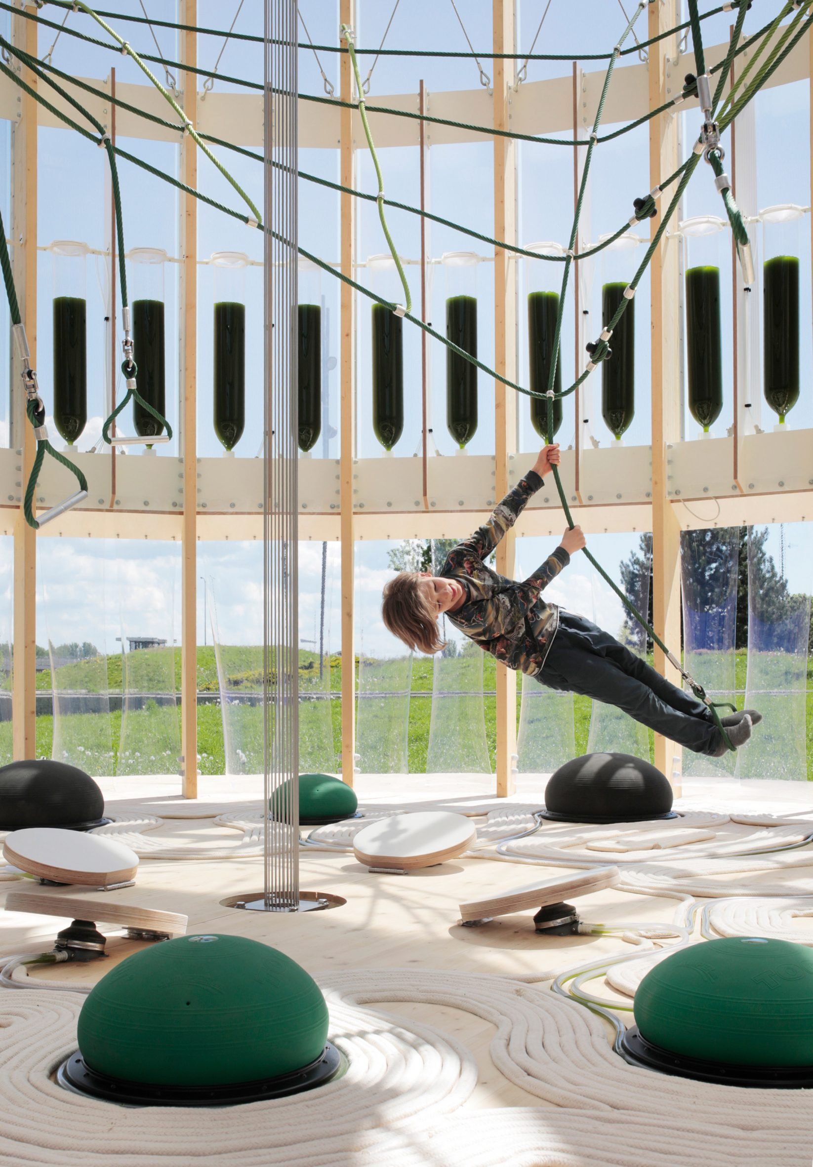 Child swinging on ropes inside the bioreactor playground