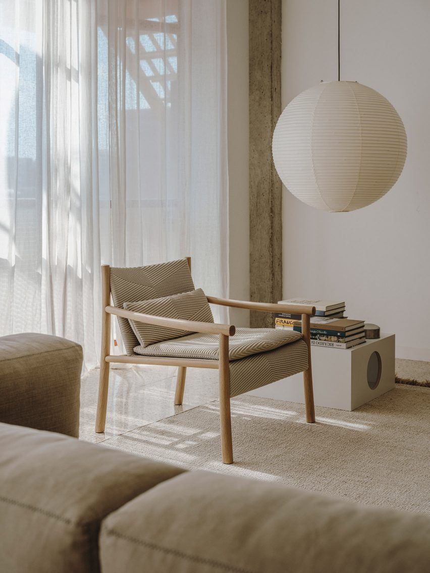 A photograph of a cream and wooden chair