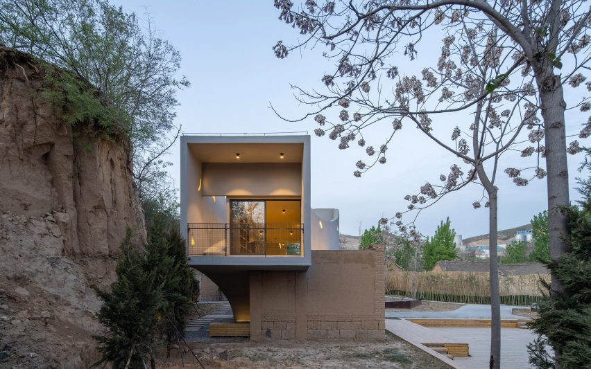 The building's fluid shapes complement the natural forms of the surrounding trees