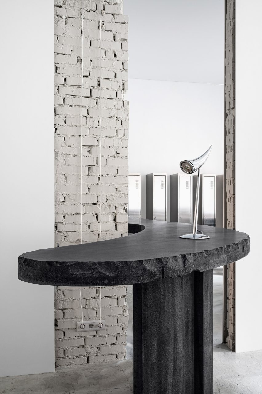 Curved concrete table with chrome light in 6:19 Studio