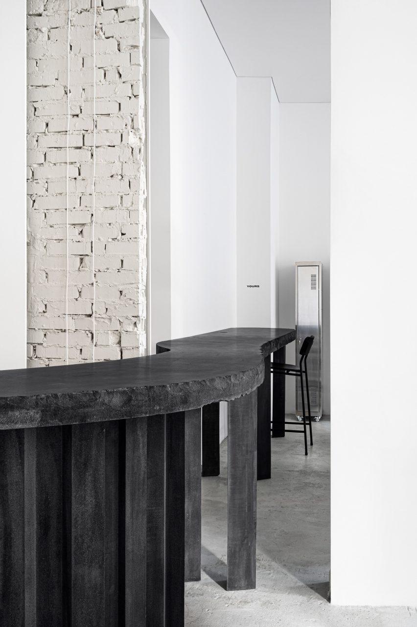 Black concrete table with high chair in tattoo parlour by Balbek Bureau