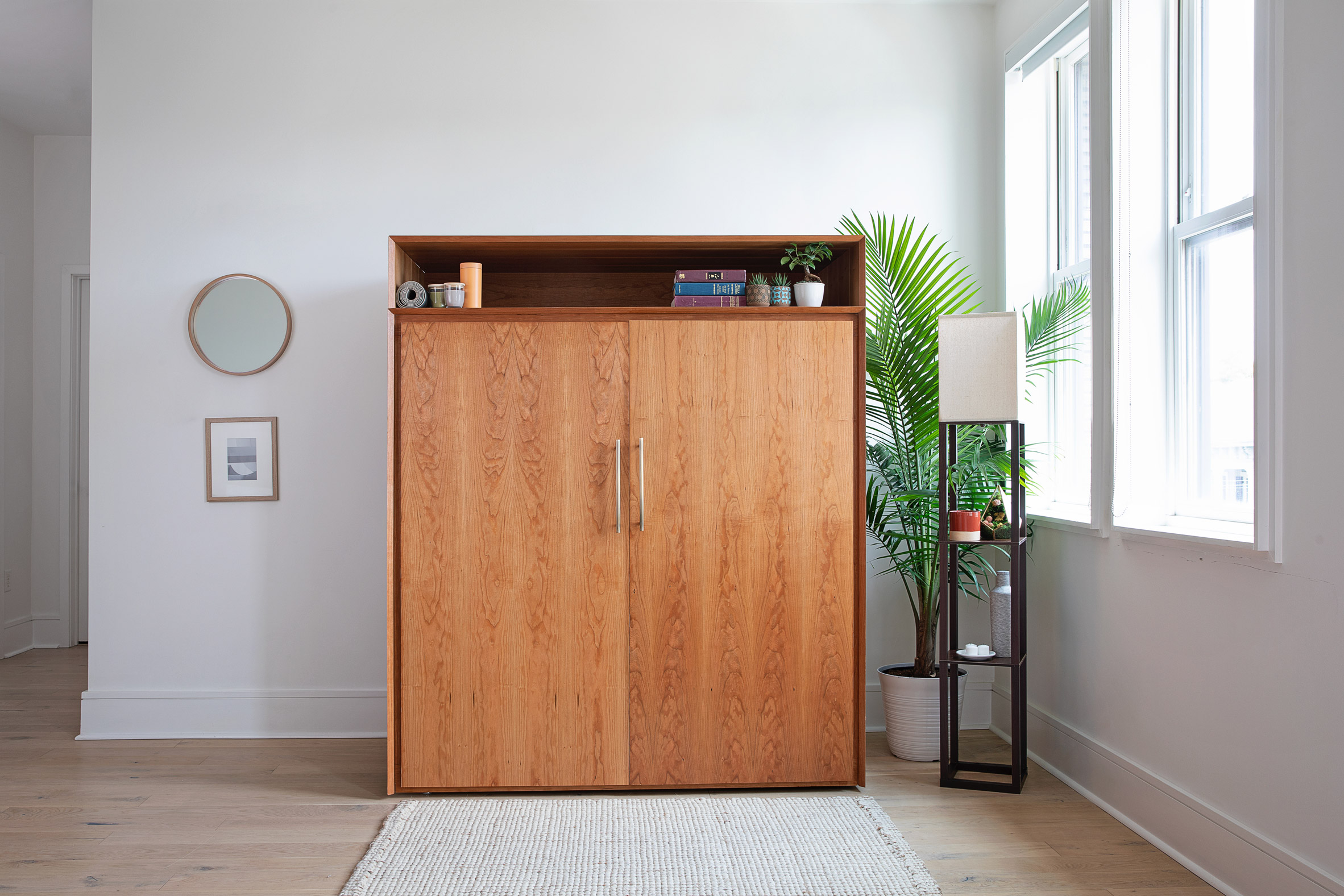 Wooden cabinet in mid-century style in a minimal white apartment hallway