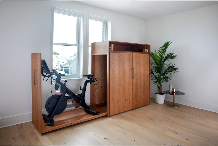 Mid-century cabinet with the full-height side drawer opened to reveal a stationary bike