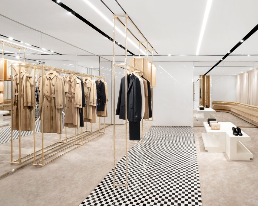 Trench coats on champagne-coloured steel shelves in No.1 Sloane Street shop by Vincenzo De Cotiis